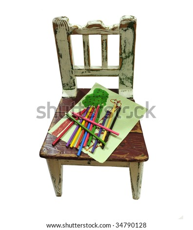 OLD CHILD'S CHAIR WITH PAPER AND PENCILS - stock photo