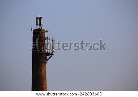 Old chimney used as a base for radio transmitters. - stock photo