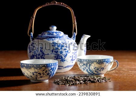 Old Chinese porcelain teapot with two cups, with green tea on the wooden desk in low key - stock photo