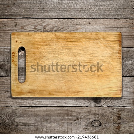 Old chopping board on wooden background - stock photo