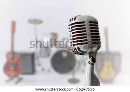 Old Chrome microphone and Blur musical instrument background - stock photo