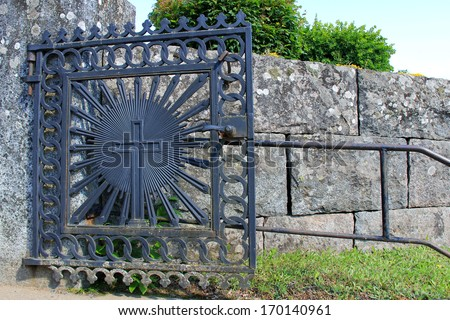 Old church gate of wrought iron with a cross. - stock photo