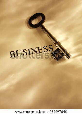 Old church key with the word business on a paper background with gold lighting and copy space.