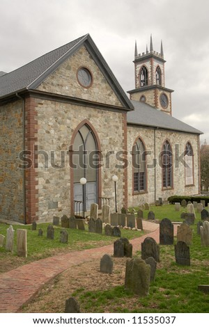 Old church road with graveyard with tombstones - stock photo