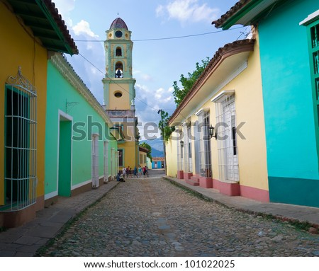 Old church sidelined by colorful houses in the colonial town of Trinidad in Cuba, a famous touristic landmark on the caribbean island - stock photo