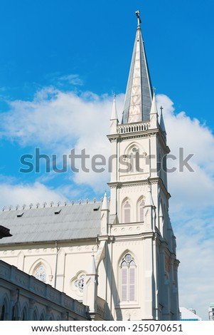 Old church turret in neoclassical style with shutters on window under blue sky. - stock photo
