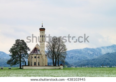 Old church with high bell tower and graveyard bellow mountains.  April weather. Wet spring snow in already fresh green grass  of meadow bellow mountains.