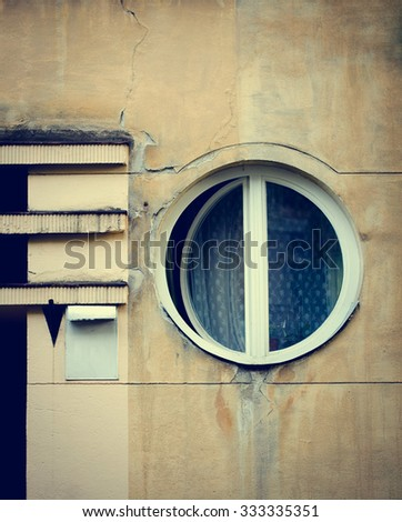 Old circle windows frame on cement cracked wall. Vintage facade.