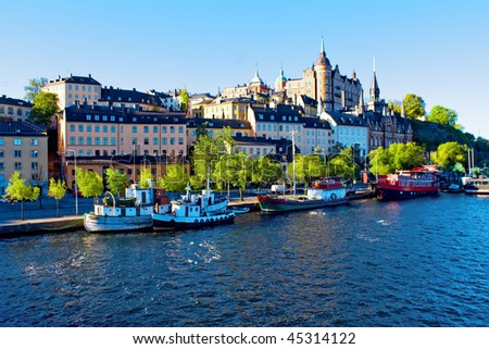 Old city buildings and old boats on water under blue sky - stock photo