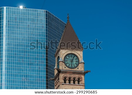 Old city hall tower with clock, against a backdrop of a modern glass facade building and a bright blue sky, gothic architecture juxtaposed with the contemporary - stock photo