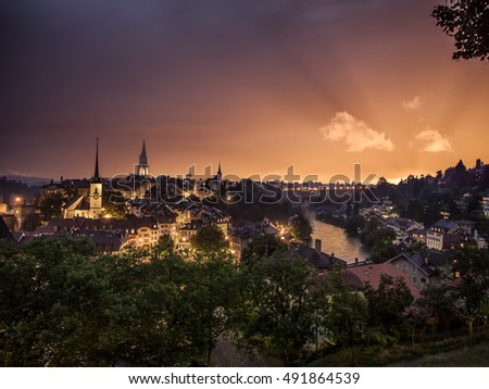 old city of bern, switzerland at dusk and city lights, wide angle shot on the old historic part of Bern City in the swiss alps as the lights turn on in town. Stunning sunset sky and epic color