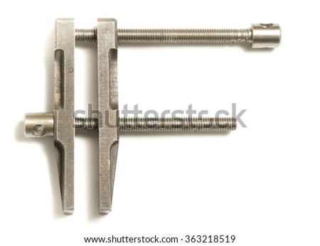 Old clamp tool on white background.