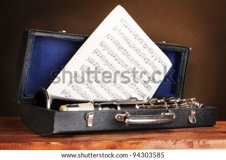 old clarinet and notebook with notes in case on wooden table on brown background - stock photo