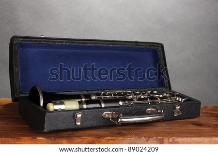 old clarinet in case on wooden table on gray background - stock photo