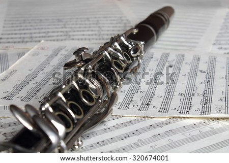 Old clarinet on the old grunge music notes close-up
