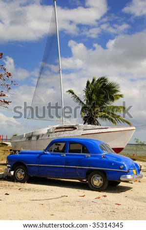 Old classic american car parked in front of sailing boat, cuba - stock photo