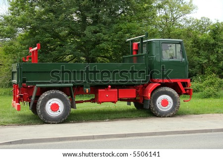 Old classic British green and red truck, standing idle on grass, with trees to the rear. - stock photo