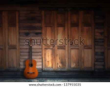old classic guitar on Texture of old Wood Door and Wall Front Home - stock photo