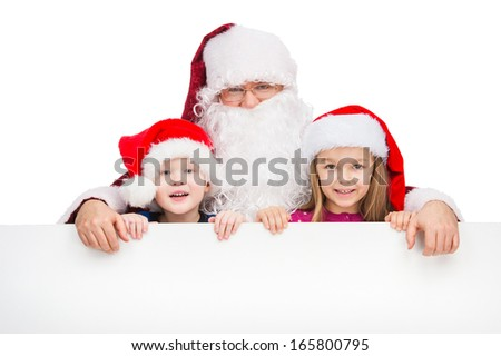 Old classic Santa Claus hugging two little kids. Standing with happy smile behind white poster isolated over white background  - stock photo