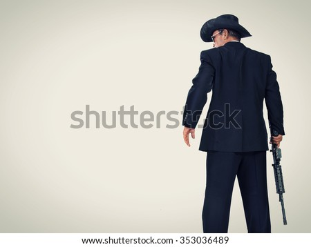 Old classic western style hitman standing with a gun, back-shot portrait in vintage color with copy space - stock photo