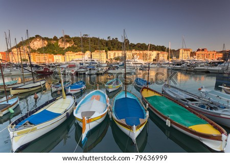 Old classic wooden boats and luxury yachts rest in the old port of Nice , cote azur, France - stock photo