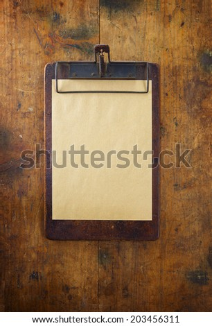 Old clipboard on old grungy wooden surface.  - stock photo