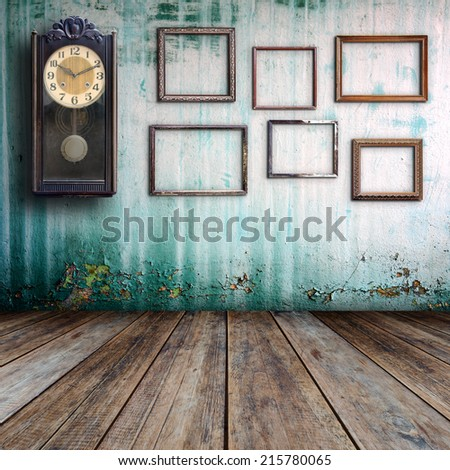 Old clock and empty picture frame in old room. - stock photo