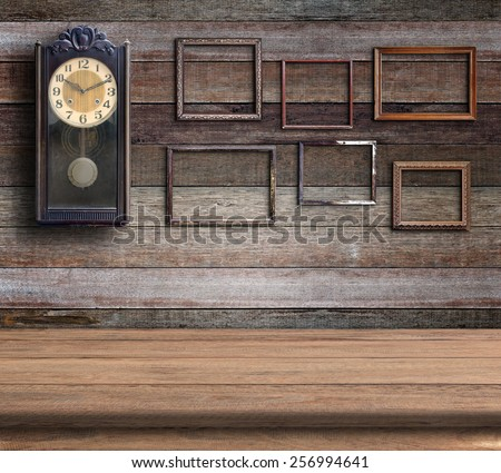 Old clock and empty picture frame in old room - stock photo