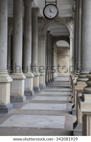 Old clock, and stone columns in Karlovy Vary, Czech Republic - stock photo