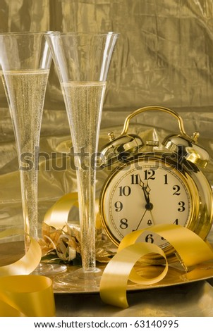 Old clock between two glasses of champagne and New Year's Eve decoration. Selective focus.