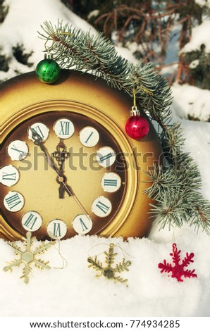 Old clock in snow with new year balls.