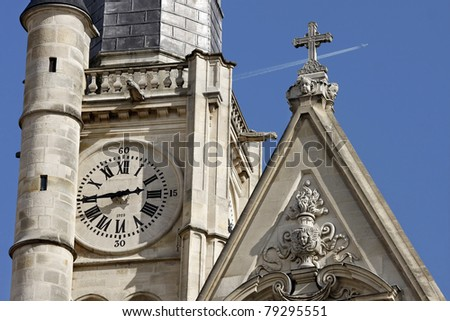 Old clock on the wall of a church of Saint Etienne du Mont, Paris, France and a jet in the background - stock photo