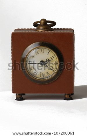 old clock with leather facing and roman numeral dial isolated on white - stock photo