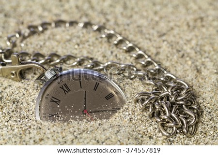 Old clock with roman numerals on the dial, lie on the sand. - stock photo