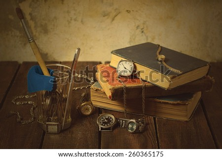 Old clocks, books, glass, tools on a wooden background. Selective focus. Toned photo - stock photo