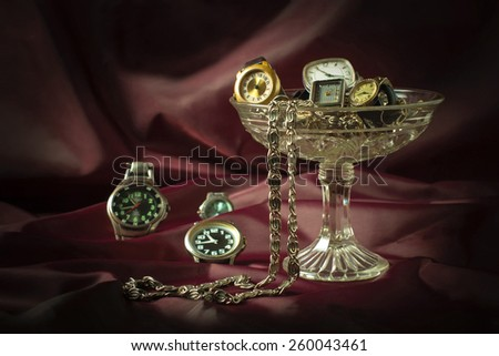 Old clockwork mechanical watches and chain in a glass vase on a burgundy background. Vintage style. Selective focus  - stock photo