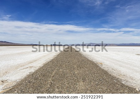 Old closed road crossing vast salt flat dry lake in California's Mojave National Preserve.   - stock photo