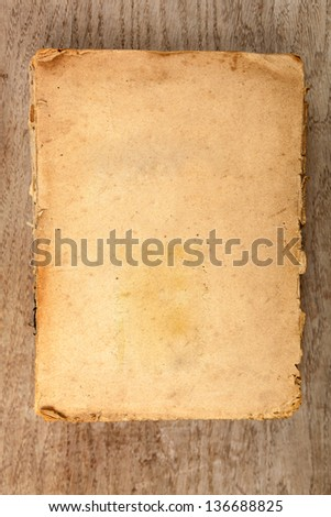 Old closed softcover book with yellowed pages on a wooden background