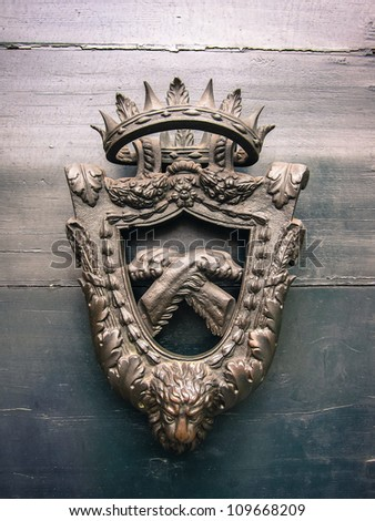 Old coat of arms with the head of a lion below realistic crossed paws in the central shield surmounted by a crown - stock photo