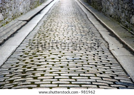 old cobbled street with stone walls - stock photo