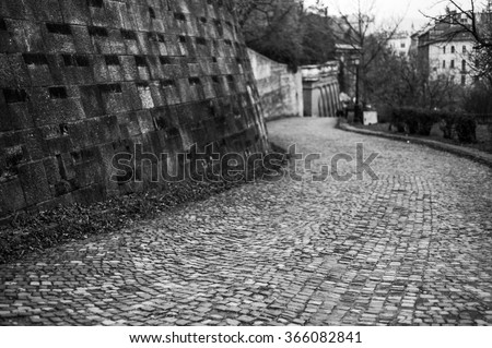 Old cobblestone paved promenade walkway in the Buda Castle, Budapest, Hungary, black and white image - stock photo