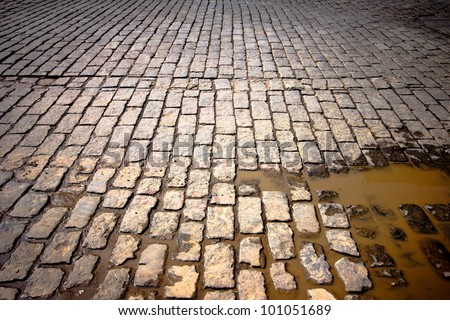 Old cobblestone street in disrepair with muddy puddle - stock photo