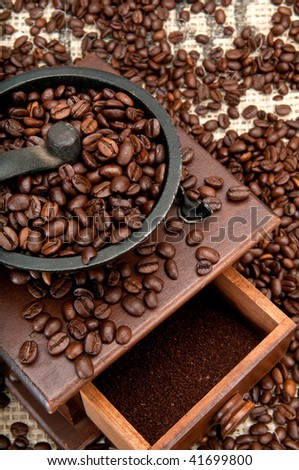 Old coffee grinder and coffee beans over burlap. - stock photo