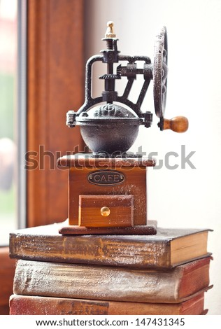 Old  coffee grinder on a stack of books - stock photo