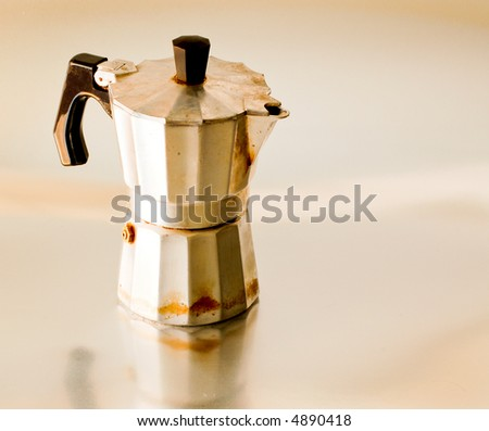 Old coffee-maker on metallic surface. - stock photo