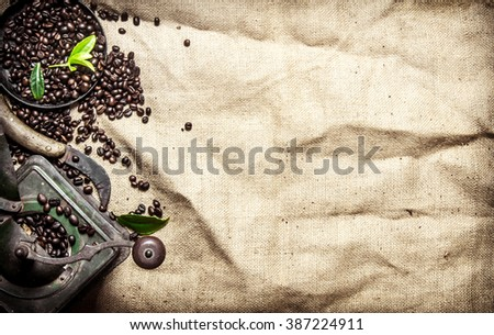Old coffee style. Roasted grain coffee with cinnamon and different old tools. On textile sack. - stock photo