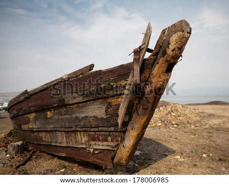 Old collapsed wooden boat close up on a sandy beach.