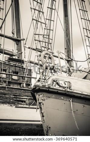Old collapsing sailboats at the dock, close-up, sepia - stock photo