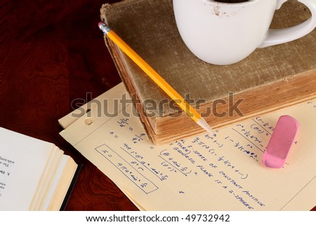 Old college physics text book and class notes with coffee cup and yellow pencil on a polished wooden table top - stock photo