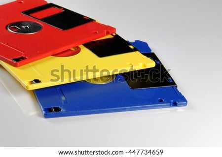 Old color floppy disk. Red, yellow and blue. - stock photo